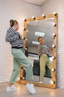 Uma jovem engraçada experimenta uma roupa olhando no espelho com lâmpadas em uma loja de roupas