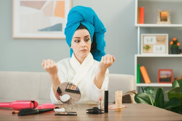 Uma jovem enrolada em uma toalha de cabelo com unhas de gel secas, sentada à mesa com ferramentas de maquiagem na sala de estar