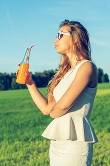 Uma jovem esbelta de óculos com cabelos cacheados sorri e bebe um coquetel laranja ou não alcoólico através de um canudo de uma garrafa em um dia ensolarado de verão