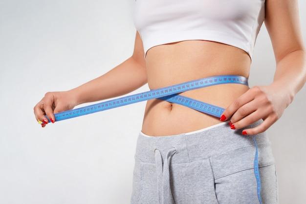 Uma jovem esbelta mede a cintura com uma fita de centímetro. na parede branca