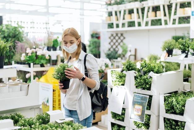 Uma jovem escolhe pequenas plantas caducas para sua casa. comprar plantas caseiras.