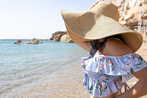 Uma jovem esconde o rosto do sol sob um grande chapéu à beira-mar.