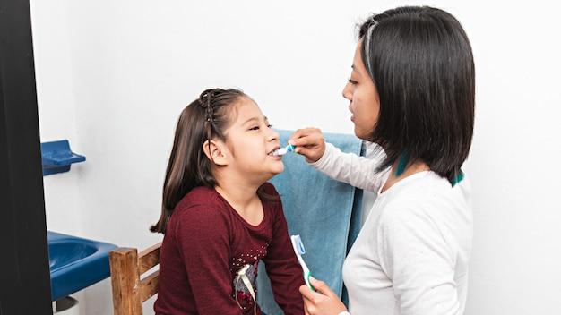 Uma jovem escovando os dentes de uma menina em um banheiro