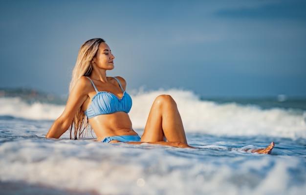 Uma jovem esguia, bronzeada, com cabelos loiros em um maiô azulado suave, sentada na areia perto do mar, apreciando o respingo das ondas frescas do mar azul