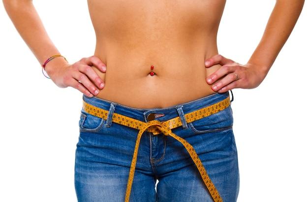 Uma jovem esguia em jeans com uma fita métrica após uma dieta bem-sucedida