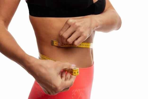 Uma jovem esguia em roupas esportivas mede sua cintura com uma fita de centímetros. fechar-se. isolado na parede branca. espaço para texto.