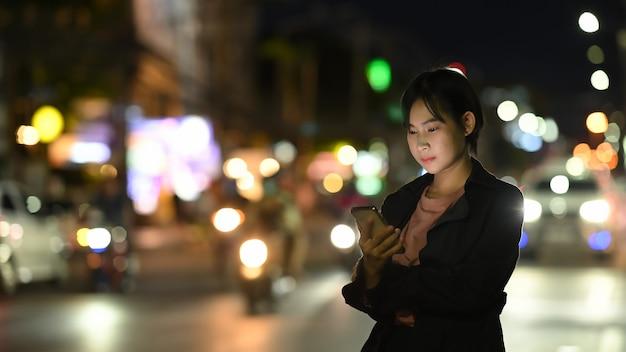 Uma jovem espera seu táxi particular enquanto usa um aplicativo de transporte no celular Foto Premium