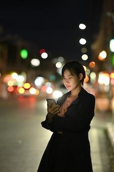 Uma jovem espera seu táxi particular enquanto usa um aplicativo de transporte no celular