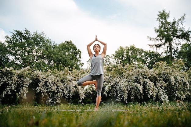Uma jovem esportista está envolvida em ioga de uma árvore em flor no parque pose de ioga da árvore vrikshasana para iniciantes