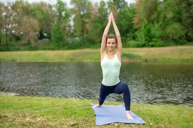 Uma jovem esportista pratica ioga em um gramado verde à beira do rio, postura de ioga assans. meditação e unidade com a natureza