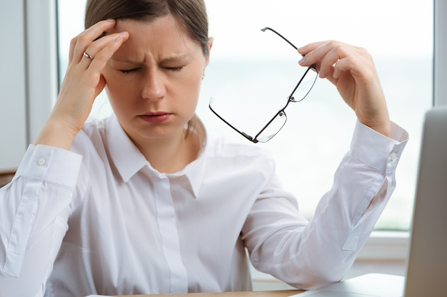 Uma jovem está com dor de cabeça no trabalho. crise de problemas financeiros chegando. um estudante exausto