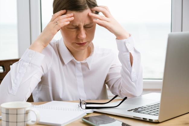 Uma jovem está com dor de cabeça no trabalho. crise de problemas financeiros chegando