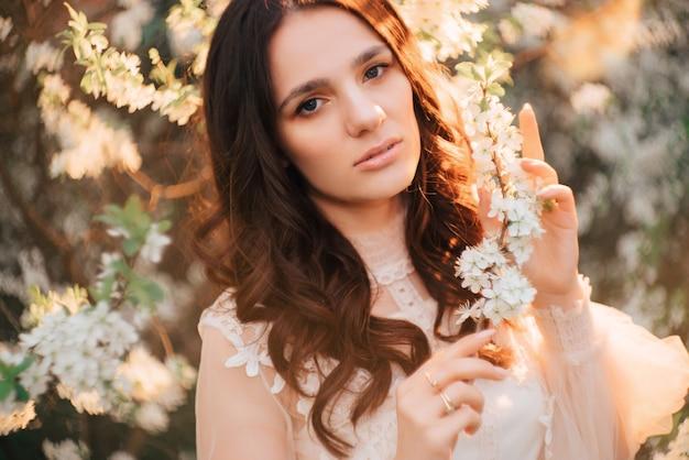 Uma jovem está contra um fundo de árvores floridas. fechar-se