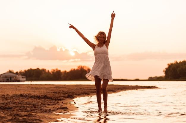 Uma jovem está dançando no contexto do pôr do sol, uma bela loira esbelta feliz em um ...