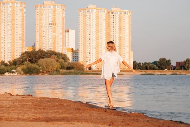 Uma jovem está de costas contra o fundo da praia, uma bela loira esguia em ...