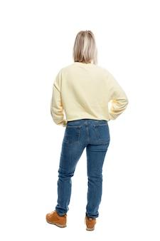 Uma jovem está de pé com as costas em pleno crescimento. loira sorridente em um suéter amarelo e jeans.