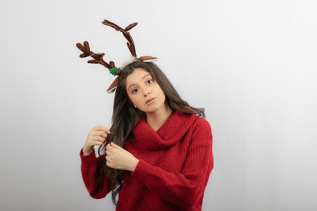 Uma jovem está de pé com uma bandana em forma de chifres de natal.