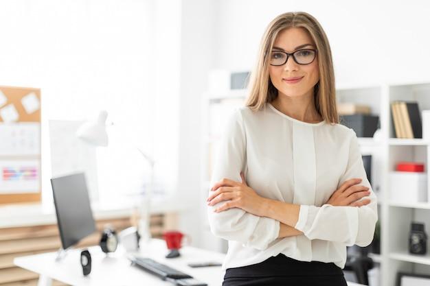 Uma jovem está de pé encostado em uma mesa no escritório.