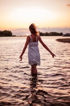 Uma jovem está de pé na água por trás de uma bela loira em um vestido de verão branco poses ...