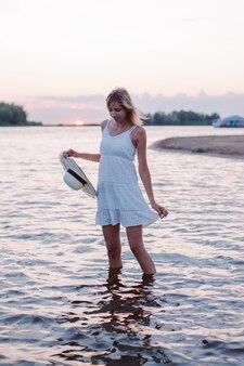 Uma jovem está de pé na água uma bela loira feliz em um vestido branco de verão no backg ...