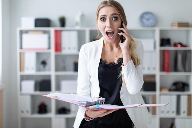 Uma jovem está de pé no escritório ao lado das prateleiras, falando no telefone e segurando uma pasta com documentos.