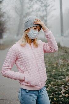 Uma jovem está de pé perto da estrada com uma máscara médica segurando a cabeça com as mãos. dor de cabeça no inverno na rua.