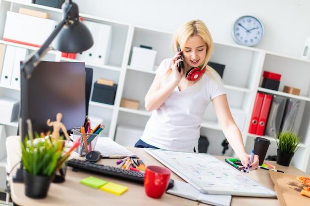 Uma jovem está de pé perto de uma mesa, falando ao telefone e segurando um marcador na mão sobre a mesa é uma placa magnética no pescoço, fones de ouvido da menina pendurar