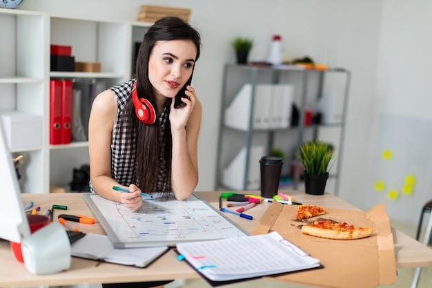 Uma jovem está de pé perto de uma mesa, segurando um marcador verde na mão e falar ao telefone
