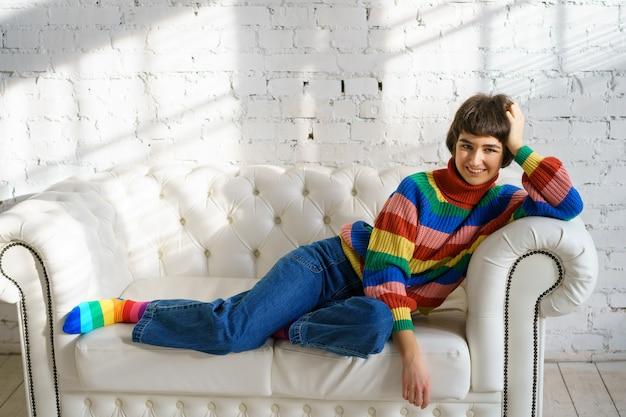 Uma jovem está deitada em um sofá com um suéter multicolorido e meias