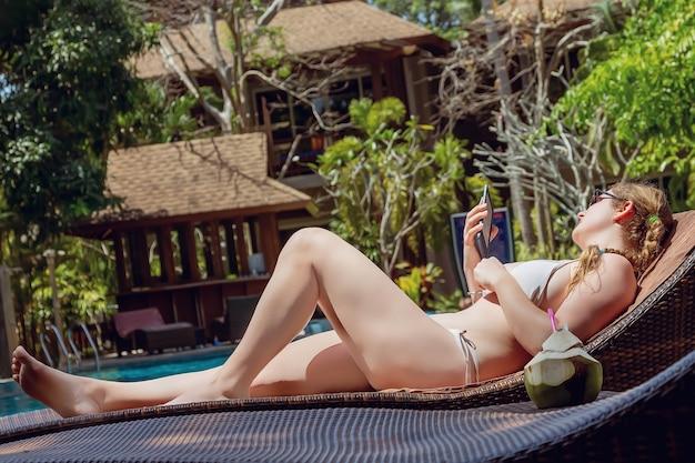 Uma jovem está deitada em uma espreguiçadeira à beira da piscina e lendo um e-book. perto está o suco de coco fresco.
