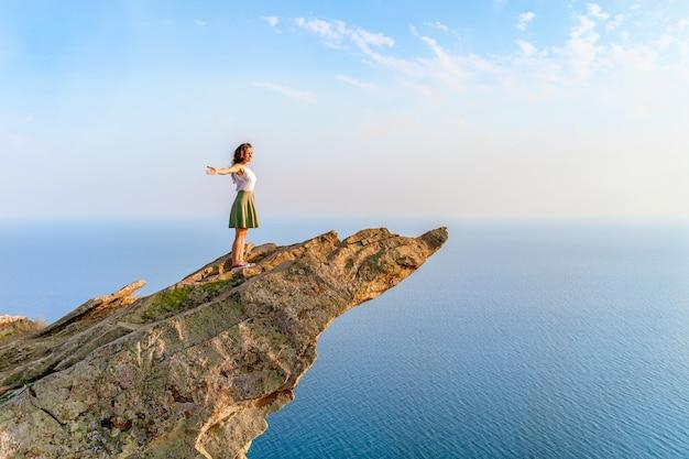 Uma jovem está em um penhasco íngreme pitoresco acima do mar contra o céu