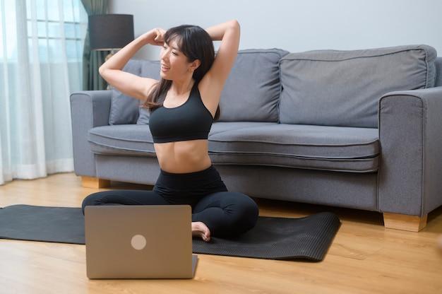 Uma jovem está exercitando e assistindo a aula de fitness de treinamento online no laptop na sala de estar em casa, esporte, fitness e conceito de tecnologia.
