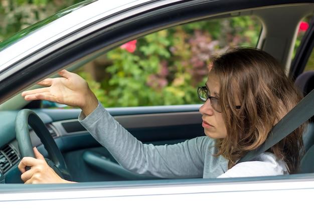 Uma jovem está indignada sentado no carro durante um engarrafamento.