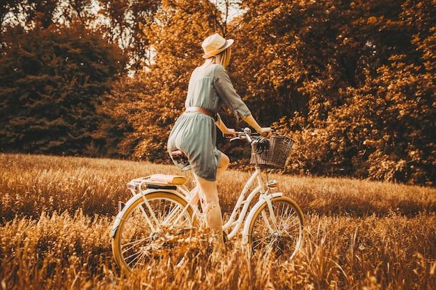 Uma jovem está lendo um livro sobre um fundo de uma bicicleta retrô.