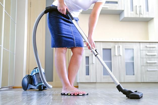 Uma jovem está limpando o apartamento. nas mãos de um eletrodoméstico, aspirador de pó.