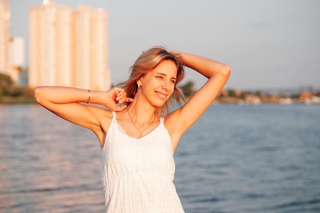 Uma jovem está no fundo do retrato da cidade de uma bela loira bronzeada sorridente ...