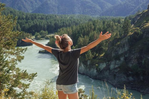 Uma jovem está no topo de uma montanha e abre os braços no fundo de uma paisagem