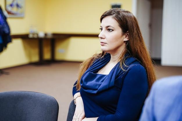 Uma jovem está ouvindo na conferência ou seminário.