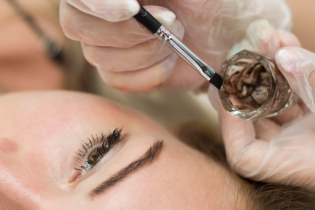 Uma jovem está passando por um procedimento para corrigir e colorir as sobrancelhas. mestre de cozinhar henna em uma xícara especial.
