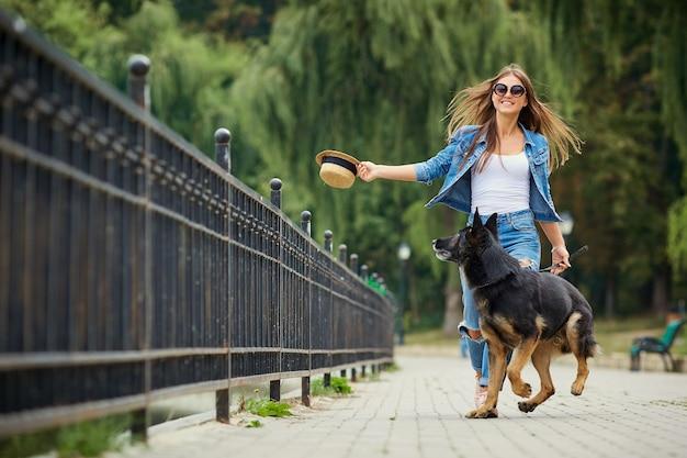 Uma jovem está passeando com um cachorro no parque