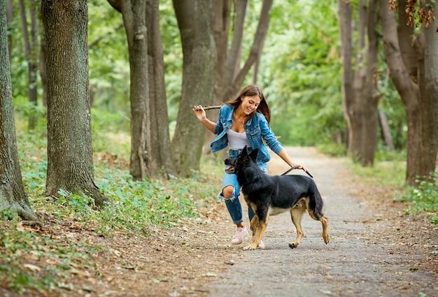 Uma jovem está passeando com um cão pastor alemão
