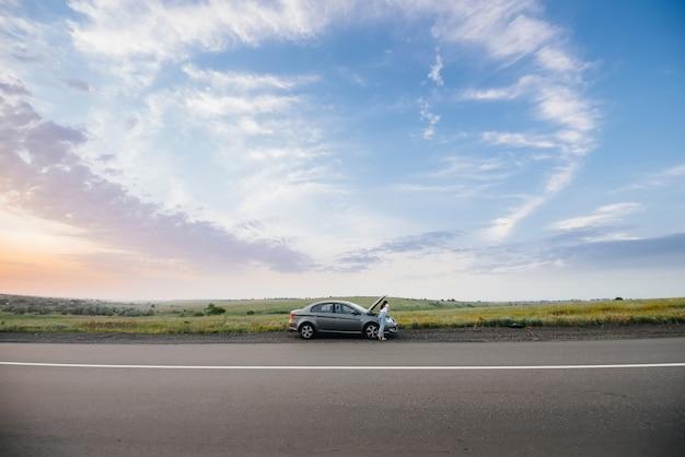 Uma jovem está perto de um carro quebrado no meio da rodovia durante o pôr do sol e tenta pedir ajuda ao telefone. avaria e reparação do carro. esperando por ajuda.