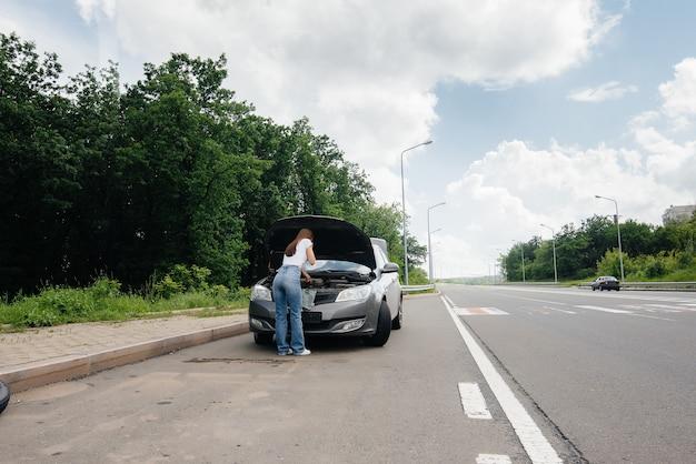 Uma jovem está perto de um carro quebrado no meio da rodovia e pede ajuda ao telefone. avaria e avaria do carro. esperando por ajuda.