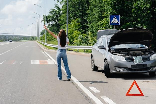 Uma jovem está perto de um carro quebrado no meio da rodovia e pede ajuda ao telefone, enquanto tenta parar os carros que passam. avaria e avaria do carro. esperando por ajuda.
