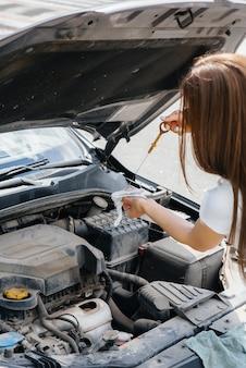 Uma jovem está perto de um carro quebrado no meio da rodovia e verifica o nível de óleo do motor. avaria e avaria do carro. esperando por ajuda.