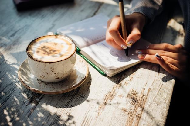 Uma jovem está sentada à mesa perto da janela e escrevendo em um caderno.