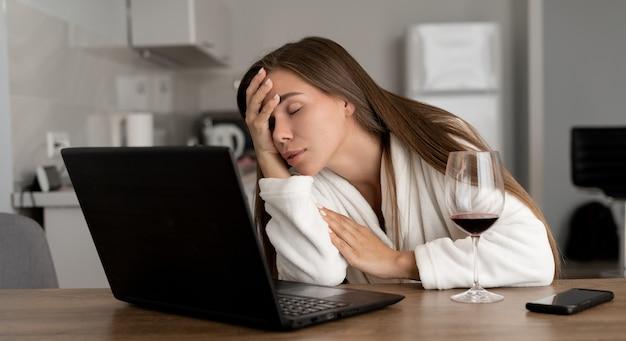 Uma jovem está sentada em casa em um laptop. fadiga e excesso de trabalho.