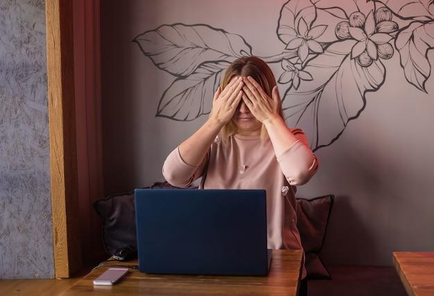Uma jovem está sentada em um café com um laptop e cobre os olhos com as mãos