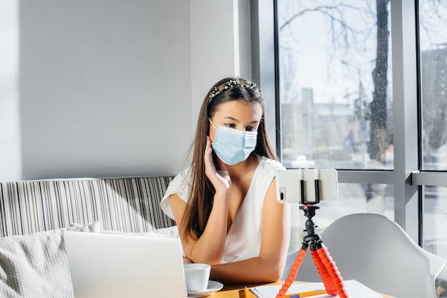 Uma jovem está sentada em um café com uma máscara e conduz um videoblog. comunicação com a câmera.