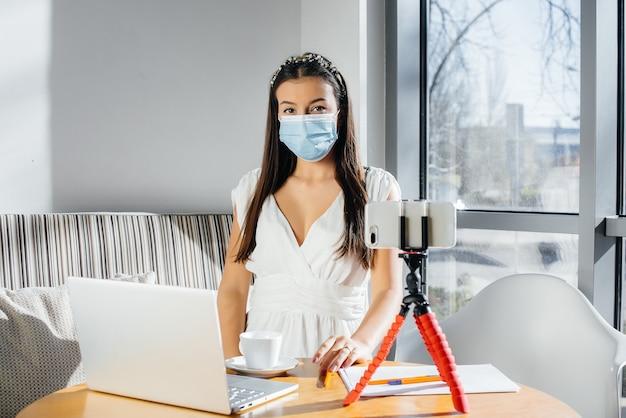 Uma jovem está sentada em um café com uma máscara e conduz um videoblog